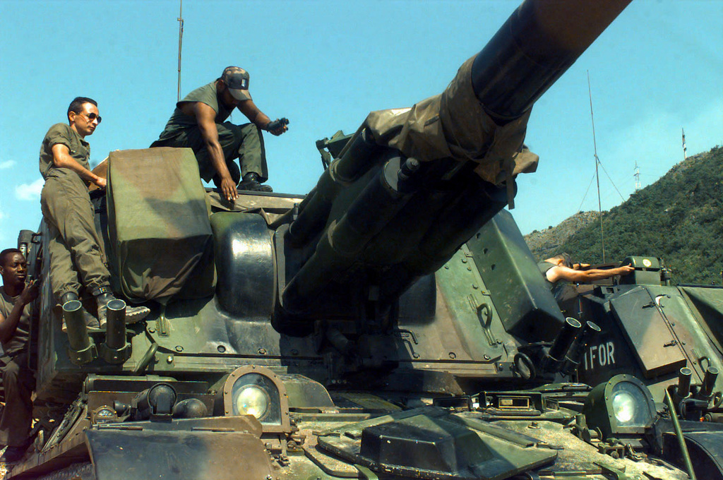 Two French Army Giat 155mm GCT (155mm AUF1) Self-propelled Guns, 40th Regiment d' Artillerie, with IFOR markings are parked at Hekon base, near Mostar, Bosnia-Herzegovina, in support of Operation Joint Endeavor. Both guns have the IFOR marking on their turrets. Three crewmembers are seated or standing on the turret of the vehicle in the foreground and one crewmember is inspecting the vehicle in the background. Operation Joint Endeavor is a peacekeeping effort by a multinational Implemention force (IFOR), comprised of NATO and non-NATO military forces, deployed to Bosnia in support of the Dayton Peace Accords