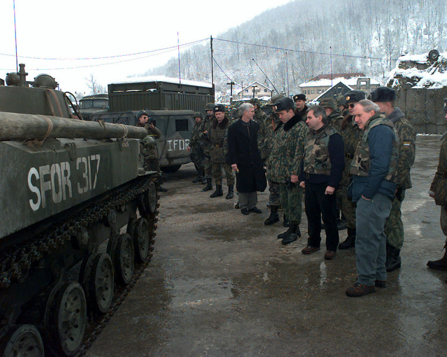 US Senator Carl Levin (Michigan), and US Senator Jack Reed (Rhode Island), and Mr. Debeboes, standing beside Russian and US soldiers, look at a parked Russian BMD-2 Airborne Combat Vehicle, with SFOR markings, during their visit to the Russian Airborne Brigade in Tojsici, Bosnia-Herzegovina. Both Senators are visiting US forces involved in Operation Joint Guard. Operation Joint Guard is a peacekeeping effort by a multinational Implementation Force (IFOR), comprised of NATO and non-NATO military forces, deployed to Bosnia in support of the Dayton Peace Accords