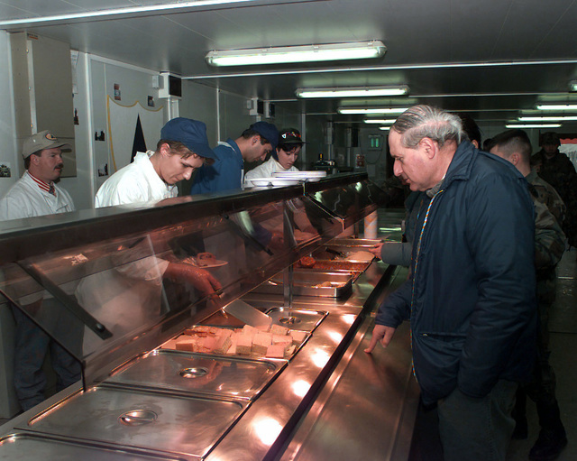 US Senator Carl Levin (Michigan) is served food while standing in the food line in the TF1-26 Dining Facility at Camp Dobol, Bosnia-Herzegovina. The Senator is visiting US forces involved in Operation Joint Guard. Operation Joint Guard is a peacekeeping effort by a multinational Implementation Force (IFOR), comprised of NATO and non-NATO military forces, deployed to Bosnia in support of the Dayton Peace Accords