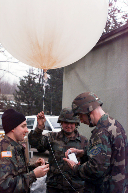 Private First Class Adrenne King, Headquarters Battalion Division, holds a weather balloon as SENIOR AIRMAN Bruce Frost and STAFF Sergeant Glenn Zilkenat get the Radiosande weather detection device prepared. The weather balloon will send back temperature, dew point, and wind speed readings around the Tuzla AB area