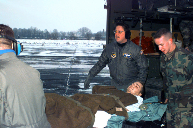 Members of the 86th Aeromedical Evacuation Squadron, Ramstein AB, Germany load SPECIALIST Martin Begosh, 709th Military Police Battalion, into the back of a C-130 Hercules for medical evacuation from Taszar, Hungary. SPECIALIST Begosh received the Purple Heart for injuries he received when the High-Mobility Multipurpose Wheeled Vehicle (HMMWV) he was driving struck a land mine in northern Bosnia-Herzegovina