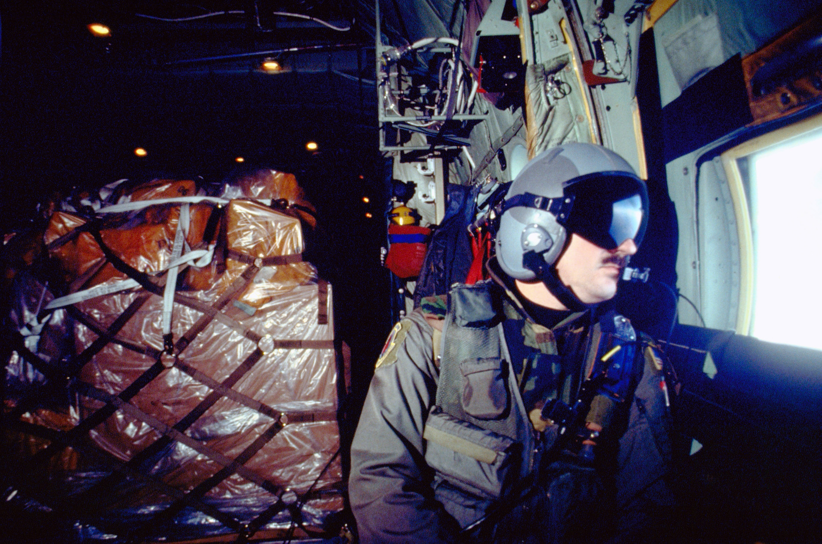 Loadmaster, MASTER Sergeant Kevin Hanoi from the 50th Airlift Squadron, Little Rock AFB, Arkansas, keeps alert as he watches out the window of the C-130 Hercules aircraft for hostile action such as Surface to Air (SAM) missiles and Anti-Aircraft Armament (AAA). If hostile action is seen MASTER SGT. Hanoi notifies the pilot who would take evasive action or fire a flare. The 50th AS is on temporary duty from Arkansas to Ramstein. Wearing flight helmets, kevlar and life survival vests, the crew flies missions from Ramstein Air Base, Germany into Bosnia-Herzegovina in support of the Implementation Force (IFOR) mission. The IFOR mission is to ensure that the former warring nations of Serbia, ...