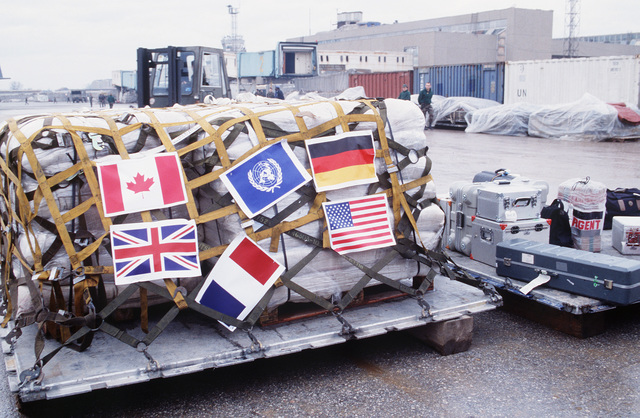 Paper flags representing six participating nations are attached to the last pallet of supplies as part of the Sarajevo Air Bridge Humanitarian Aid termination ceremony. The longest humanitarian airlift in history is ending. During the past three and one half years the operation has provided 160,000 metric tons of supplies in 12,900 sorties involving 21 nations