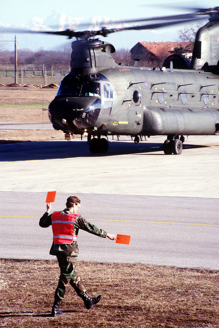 SENIOR AIRMAN Brice King, 31st Maintenance Squadron, Aviano AB, Italy, marshals out a Chinook CH-47. AIRMAN King is responsible for recovering and maintaining all NATO and Transient Aircraft in support of Operation Joint Endeavor
