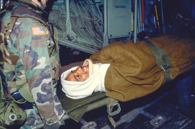 One of the five patients injured while participating in Joint Endeavor at Tuzla Air Base, Bosnia, is carried on a stretcher by members of the 23rd Aero-Medical Evacuation Squadron, Pope AFB, North Carolina onto a C-130 Hercules aircraft from the 50th Airlift Squadron, Little Rock AFB, Arkansas, deployed to Ramstein Air Base, Germany