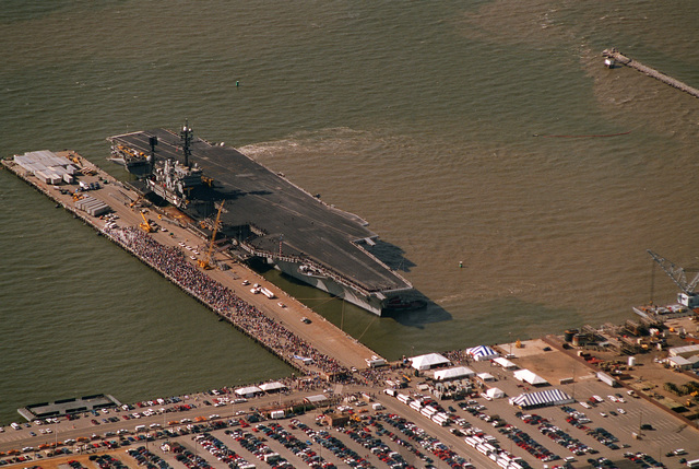 Aerial starboard bow view of the aircraft carrier USS America (CV-66) completing mooring at pier 12 upon return from its final Mediterranean deployment. Friends, relatives and love ones wait on the pier for the crew to start disembarking