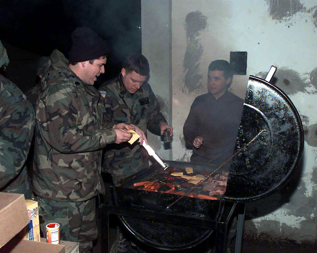 CAPT Mark Hamill (USAF), 621st TALCE (Tanker Airlift Control Element), MAJ Jeff Walker (USAF), STAFF Judge Advocate, and Special Agent Joe Derdzinski, AFOSI (Air Force Office of Special Investigation) cook ribs and hamburgers, at the base of the control tower, for troops deployed to Tuzla Air Base, Bosnia-Herzegovina, in the support of Operation Joint Endeavor. Operation Joint Endeavor is a peacekeeping effort by a multinational Implementation Force (IFOR), comprised of NATO and non-NATO military forces, deployed to Bosnia in support of the Dayton Peace Accords