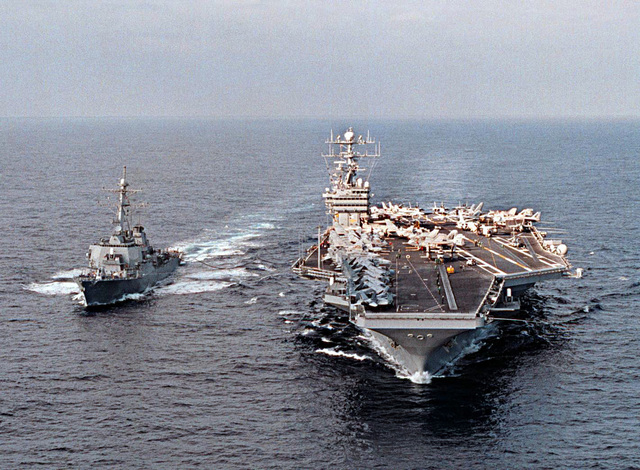 Straight on, bow shot ot the U.S. Navy's nuclear powered aircraft carrier; the Nimitz Class, USS GEORGE WASHINGTON (CVN 73) (right), as it refuels the Arleigh Burke class guided missile destroyer USS STOUT (DDG 55) while transiting the Atlantic Ocean on January 30, 1996. This marked the first time the STOUT came alongside an aircraft carrier for underway replenishment
