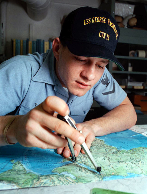On board the USS George Washington (CVN-73), located in the Adriatic Sea, Quarter MASTER Third Class Jonathan Tipa practices laying navigational tracks in the Chart House. The USS George Washington is in the Adriatic Sea for a six month deployment supporting Operation Joint Endeavor