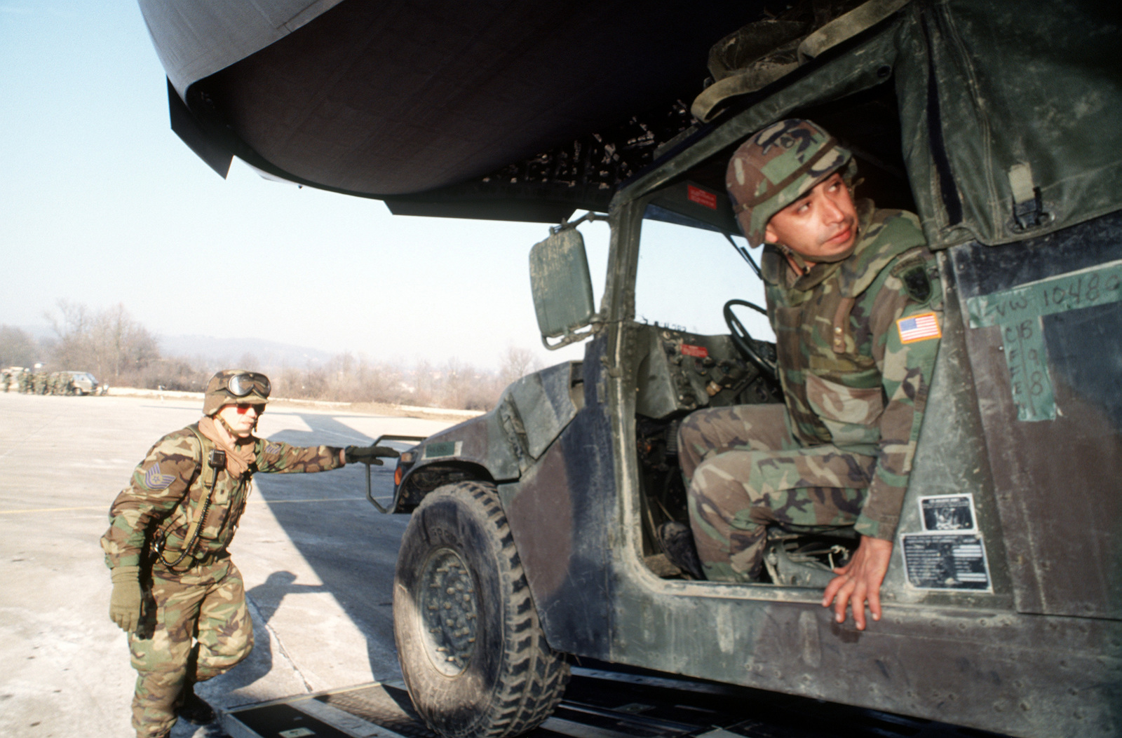 TSG Stewart Smith (right), of 621st Aerial Port Squadron, McGuire Air Force Base, New Jersey, directs SPC William Arnold of Delta Battery, 319th Field Artillery, Vicenza, Italy, as he backs up the High-Mobility Multipurpose Wheeled Vehicle (HMMWV) into the C-17 Globemaster III for redeployment during JOINT ENDEAVOR
