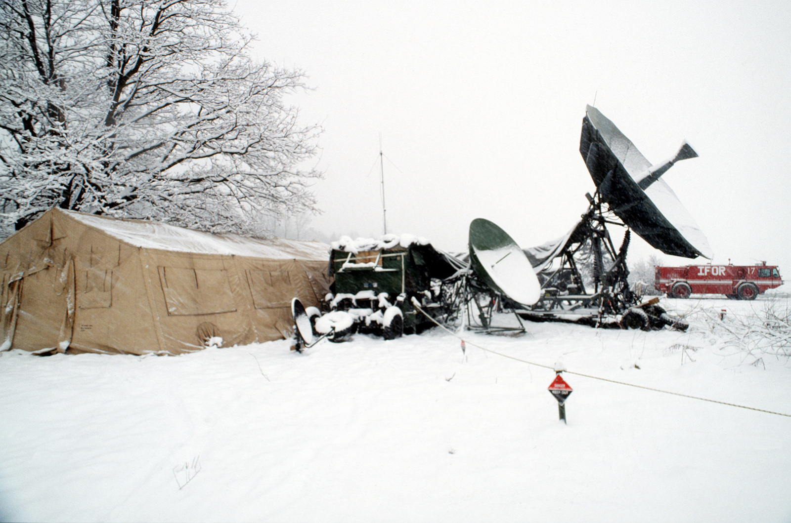 Satellite communication antenna set up by the 1ST Combat Communications Squadron, Ramstein Air Base, Germany, is covered with a fresh layer of snow during JOINT ENDEAVOR. In the background is seen a fire truck with the letters IFOR for Implementation Forces