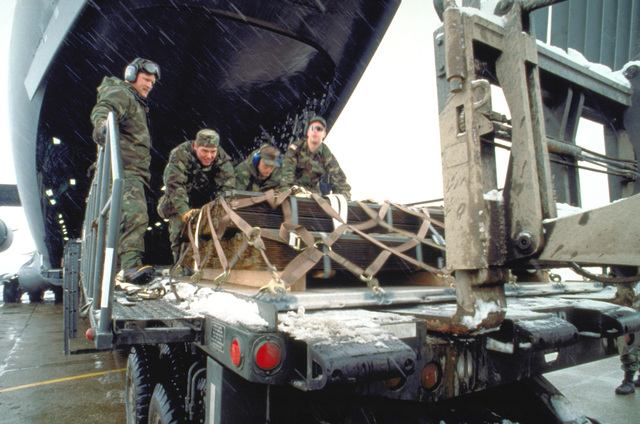 At Tuzla Air Base, Bosnia, members of the 62nd Aerial Port Squadron, McChord AFB, Washington push a pallet of metal fencing off of the C-17 Globemaster III aircraft. They're deployed to Tuzla in support of Operation Joint Endeavor. The base and personnel assigned are part of the Implementation Force (IFOR) mission. The IFOR mission is to ensure that the former warring nations of Serbia, Bosnia-Herzegovina and Croatia honor the Dayton Peach Accord to cease fire and maintain permanent borders