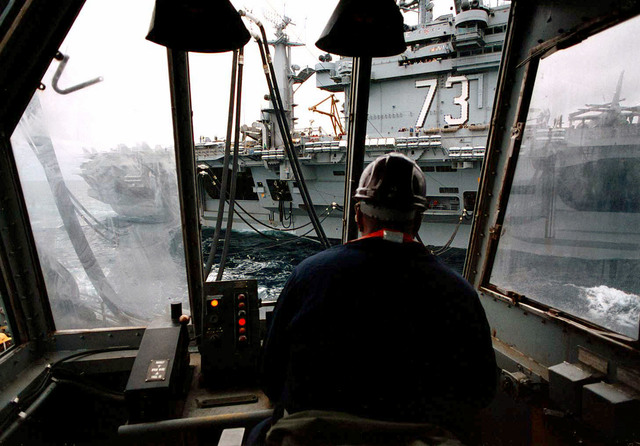 On board the Cimarron Class Oiler, USS Merrimac (AO-179), located in the Eastern Atlantic Ocean, a Deck Department crewmember controls tension on the saddle refueling lines during an underway replenishment with the nuclear powered aircraft carrier, USS George Washington (CVN-73). Both ships are on their way to the Adriatic Sea in support of Operation Joint Endeavor