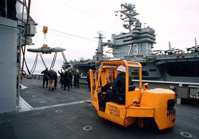 On board the Cimarron Class Oiler, USS Merrimac (AO-179), located in the Eastern Atlantic Ocean, crewmembers receive a cargo transfer of an aircraft fuel tank from the USS, George Washington (CVN-73). In the foreground, a forklift stands by to assist. The two ships are on their way to the Adriatic Sea in support of Operation Joint Endeavor