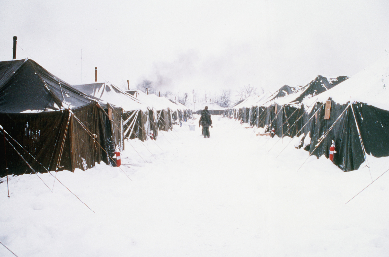 A snow covered walkway leads to tents housing Navy Seabees  Nearly