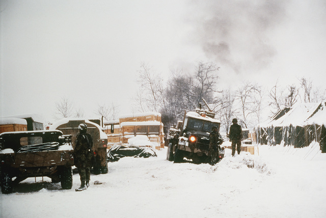 Snow covered mud makes vehicle and personnel movement around the Naval Mobile Construction Battalion 133 (NMCB-133) base camp difficult at best. The Seabees are preparing to move out to build a new base camp along the zone of separation at a desolated site 50 miles north of Tuzla Air Base. The new base camp, Camp McGovern, will serve as home for the Armys 3rd Battalion, 5th Cavalry as they take part in the operation