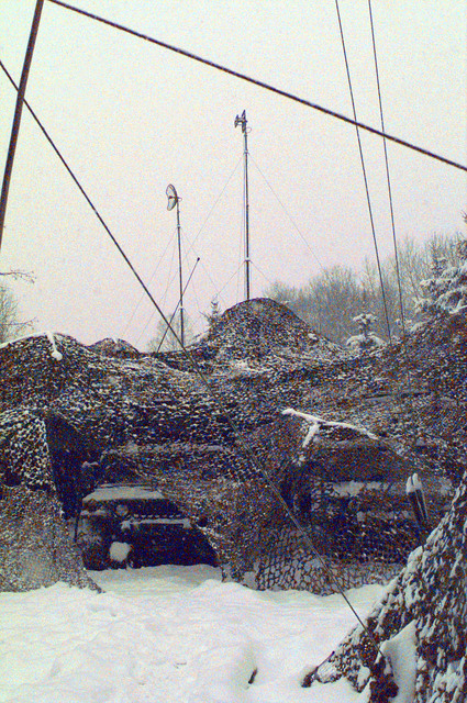 Antennas and tie-down ropes cross the sky above a camouflaged Communications Small Extension Node located on Tuzla AB, Bosnia-Herzegovina