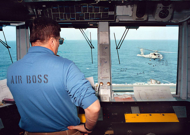 On board the USS George Washington (CVN-73), in the Adriatic Sea, Commander Robert Snyder, Air Boss, directs an SH-60 SeaHawk from Helicopter Combat Support Squadron Five, to land on the ship's flight deck