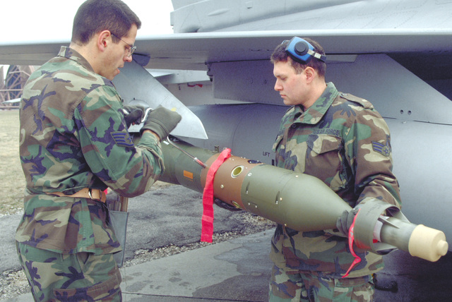 SENIOR AIRMAN Thomas Kretschmann from St Louis, Missouri and STAFF Sergeant David Sarval from Manchester, New Hampshire load a laser guided bomb on the wing of a F-16 fighting Falcon at Aviano Air Base, Italy. SENIOR AIRMAN Kretschmann and STAFF Sergeant Sarval are members of the 510th Fighter Squadron's Weapon Load Team 21. The team performed a monthly proficiency load (MPRO) as evaluators watched progress. The 510th has kept its aircraft mission ready since the inception of Operation Decisive Edge