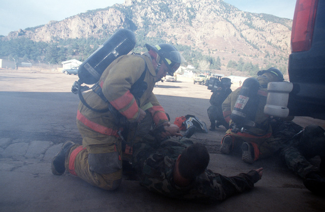 As part of the ORI a major accident involving a pick-up truck and a snow plow was staged at the Civil Engineering compound. Fire trucks and medical personnel treated the injured and removed them from the scene while fire personnel put out the fires. They were participating in the 21st Space Wing's Operational Readiness Inspection conducted at Cheyenne Mountain Air Station and Peterson AFB, Colo., 13 to 17 February 1996. The Inspector General's Team tested their ability to respond to battle conditions, power outages, mobility deployments, aircraft and automobile accidents, hostage situations, bomb threats, armed robbery, terrorism, and communication disruptions