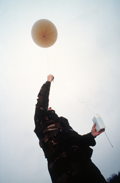 """SENIOR AIRMAN Bruce """"Jack"""" Frost, Weather Observer, Detachment 2, 617th Weather Squadron, Bad Kreuznach, Germany prepares to launch a hydrogen filled weather balloon. An RS80 radio sonde is attached to the balloon before it is released into the atmosphere where it will transmit back upper level weather conditions. The information will be used to brief pilots flying into and around Tuzla, Bosnia. SENIOR AIRMAN Frost is deployed to Tuzla to support Operation Joint Endeavor"""