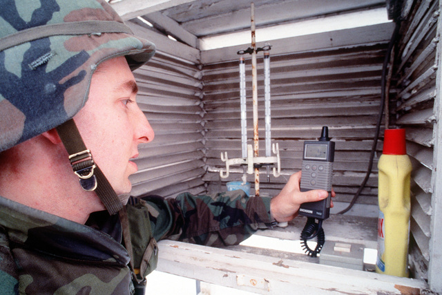 """SENIOR AIRMAN Bruce """"Jack"""" Frost, Weather Observer, Detachment 2, 617th Weather Squadron, Bad Kreuznach, Germany uses a TH550 digital temperature, humidity, dewpoint monitor to gather information that will be used to brief pilots flying into and around Tuzla, Bosnia. SENIOR AIRMAN Frost is deployed to Tuzla to support Operation Joint Endeavor"""