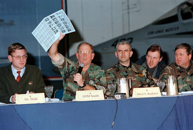 Admiral Leighton W. Smith holds up a Wanted poster during the Joint Military Commission press conference held on board the USS George Washington (CVN-73). The poster includes photos, names and descriptions of war criminals indicted by the International Criminal Tribunal from the former Yugoslavia