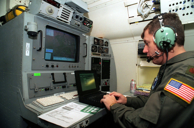 The navigation officer on a Boeing 707 aircraft, leaving Rhein Main Air Base, Germany, plots a course using a laptop computer in connection with the Joint Surveillance Target Attack Radar System (J-STARS). J-STARS is a long range, air-to-ground surveillance and battle management system. When in flight the radar can detect and track more than 120 miles of terrain providing the battle commander with invaluable information about troop movement and position. A 40-foot radome under the forward part of the fuselage houses the phased-array radar antenna. The information is fed to the 17 Army and Air Force operators who have access to the radar data in real-time via on-board large-screen graphics...