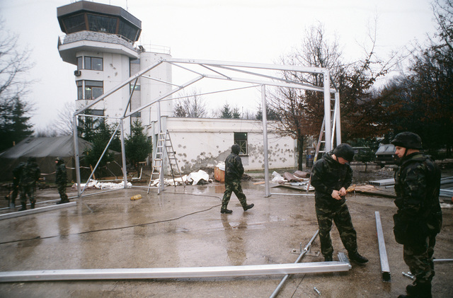 Members of the 823rd Red Horse Squadron, Hurlburt Field, Florida, and members of the 100th Civil Engineering Squadron, RAF Mildenhall, UK, assemble a tent on Tuzla Air Base, Bosnia that will be used to house fire trucks. The fire trucks belong to the 100th Civil Engineering Squadron, RAF Mildenhall, UK and are deployed to Tuzla to provide fire fghting support to the base and Operation Joint Endeavor