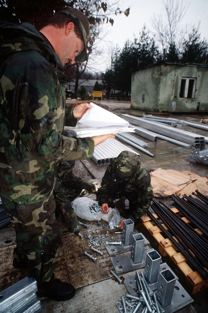 Members of the 823rd Red Horse Squadron, Hurlburt Field, Florida, organize hardware before constructing a tent to house fire trucks at Tuzla Air Base, Bosnia. The fire trucks belong to the 100th Civil Engineering Squadron, RAF Mildenhall, UK and are deployed to Tuzla to provide fire fighting support to the base and Operation Joint Endeavor