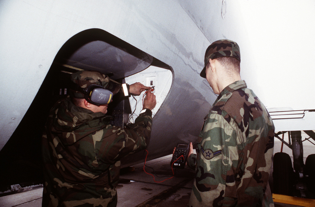 AIRMAN Hemsley assists SENIOR AIRMAN Johnson of the 375th Maintenance Squadron in checking the voltage on the C-9 Nightingale aircraft