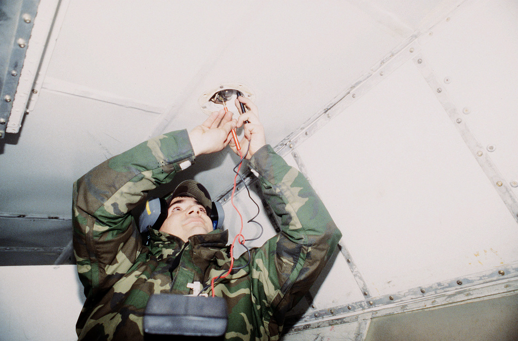 SENIOR AIRMAN Johnson of the 375th Maintenance Squadron checks the voltage from the underside of the C-9 Nightingale aircraft