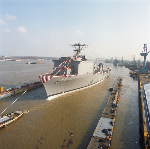 A port bow view of the dock landing ship PEARL HARBOR (LSD-52) being moved into a floating dry dock shortly after christening and launch at the Avondale Industries, Inc., Shipyards Division