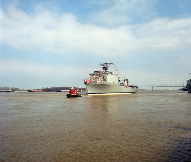 A port bow view of the dock landing ship PEARL HARBOR (LSD-52) being pulled back to the pier by a commercial tugboat following the ships christening and launch at the Avondale Industries, Inc. Shipyard on the Mississippi River