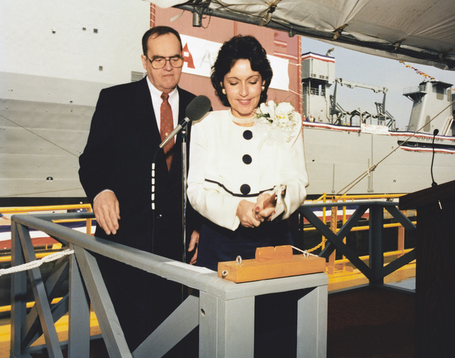 Mrs. Beverly Angello Young, Ships Sponsor of the landing ship PEARL HARBOR (LSD-52) pictured here christening the ship. Looking on is Mr. Albert L. Bossier, Jr., Chairman, President and CHIEF Executive Officer of Avondale Industries, Inc., Shipyards Division