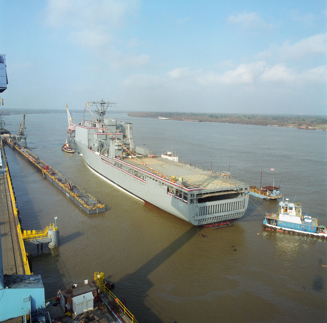 Port quarter view of the dock landing ship PEARL HARBOR (LSD-52) being moved into a floating dry dock following her christening and launch at the Avondale Industries, Inc., Shipyards Division