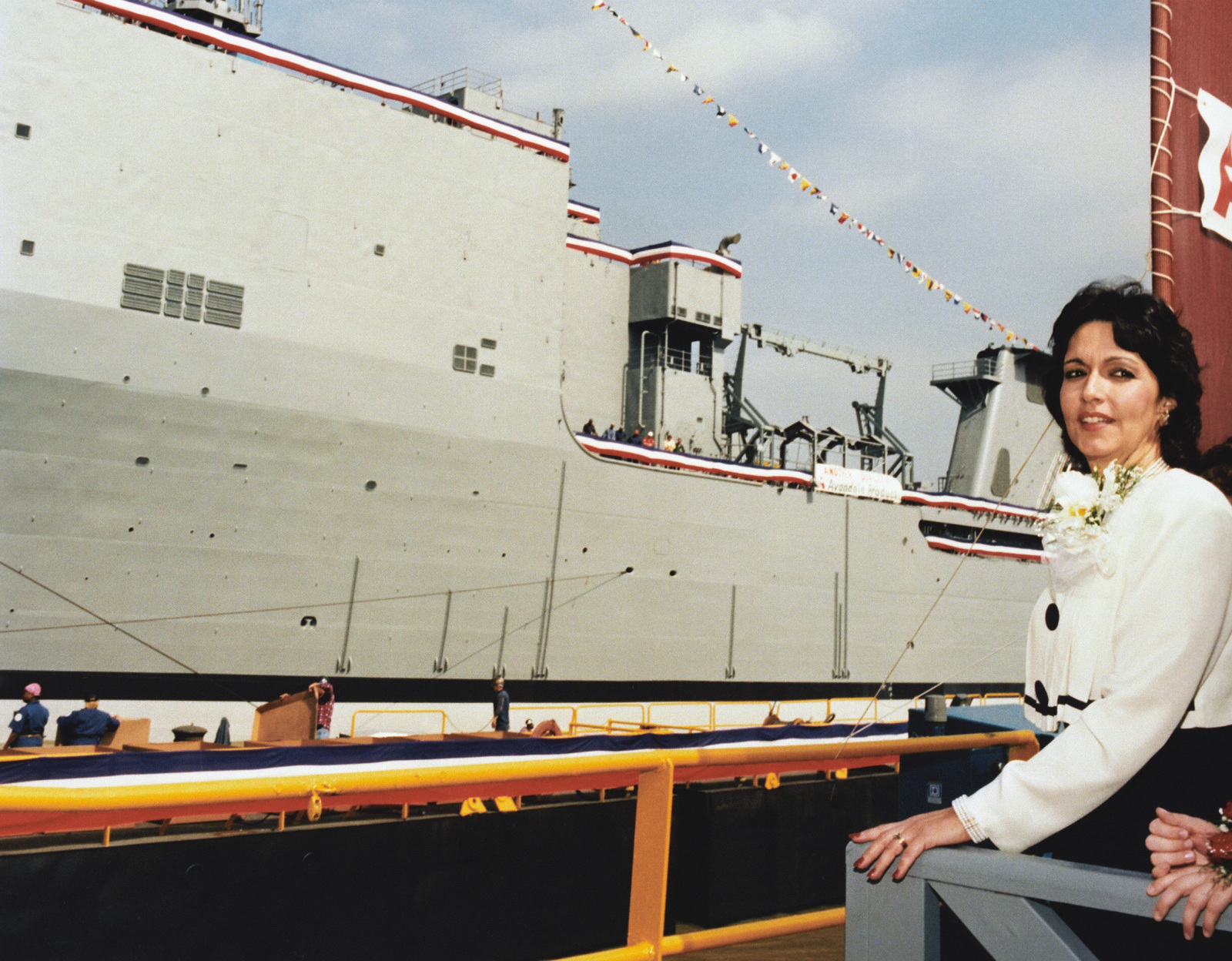 Ships Sponsor, Mrs. Beverly Angello Young, poses with the dock landing ship PEARL HARBOR (LSD-52) afloat in the Mississippi River at the conclusion of the christening and launch ceremony at Avondale Industries, Inc. Shipyards Division