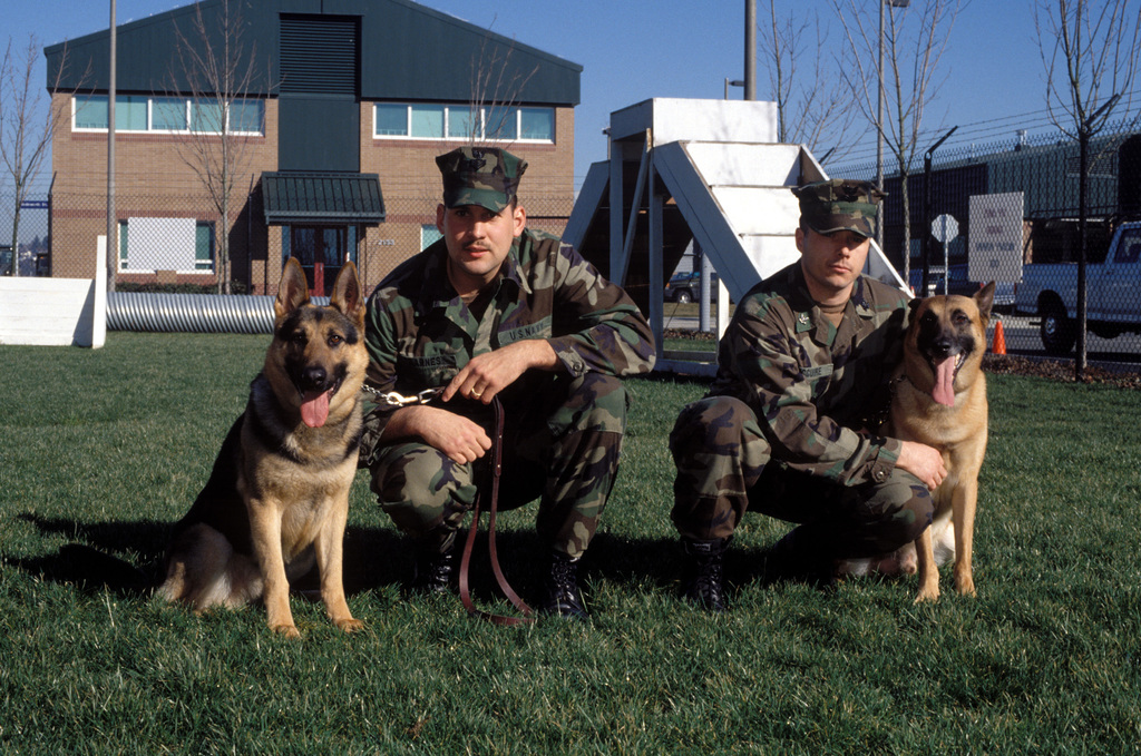 Machinist Mate First Class (MA1) Thomas Barnes and MA2 John McGuire pose during training with their working dogs at the Military Working Dog Kennel