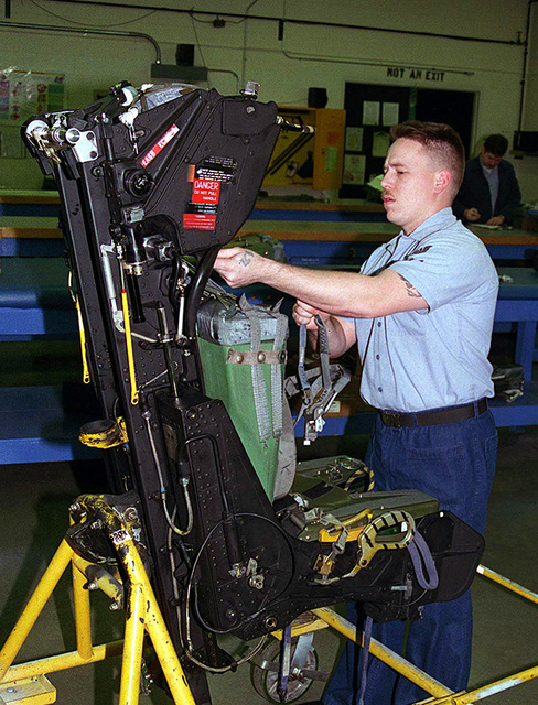 Aviation Machinist Electrician Third Class Shane Martinez, Miami, Florida, conducts a release check of an ejection seat for an EA-6B electronic counter measures Prowler