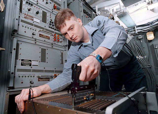 Data Systems Technician 2nd Class Michael Bostain troubleshoots an inner-communications cabinet in the Information Services Department on board the nuclear-powered aircraft carrier, USS George Washington (CVN-73), on March 5, 1996. The Washington is commanded by Captain Malcolm P. Branch and operating in the Adriatic Sea in support of the NATO-led Operation Decisive Endeavor over Bosnia Herzegovina