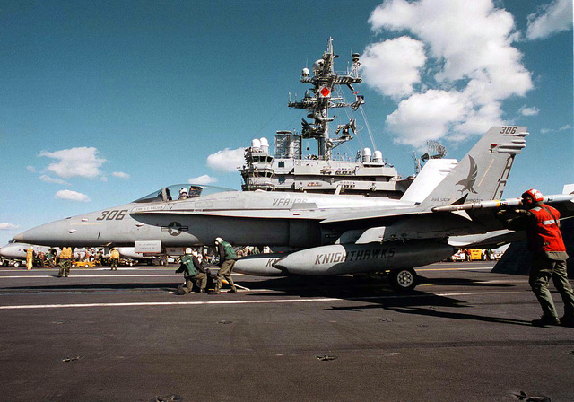 Flight deck personnel aboard the nuclear powered aircraft carrier USS George Washington (CVN-73) prepare an F/A-18C Hornet from the Knighthawks of Fighter Attack Squadron One Three Six (VFA-136) for a mission over Bosnia Herzegovina. The USS George Washington is commanded by CAPT Malcolm P. Branch and is operating in the Adriatic Sea in support of the NATO-led Operation Decisive Endeavor