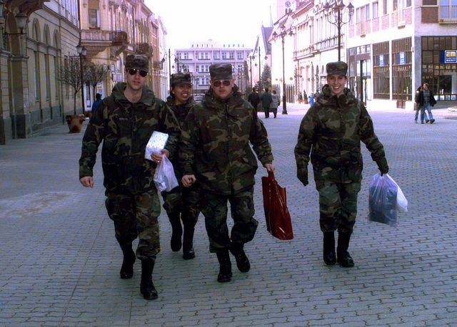 Soldiers from Taszar Barracks, Hungary, stroll the street with their shopping bags. The soldiers are allowed to participate in a cultural liaison tour, and, for the first time, visit surrounding intermediate staging base sites within HQ USAREUR (FWD) area of responsibility. They are having two fun-filled hours of downtown shopping in Kaposvar. They are required to maintain command and control in groups of four or more