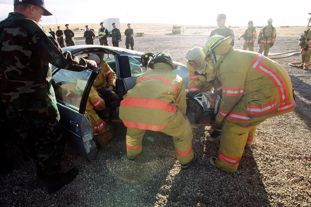 "Rescue team members successfully remove a ""victim"" from an automobile as the IG team members observe and grade the participants. The Inspector General Team tested the ability of the base to respond to battle conditions, power outages, mobility deployments, aircraft and automobile accidents, hostage situations, bomb threats, armed robberies, terrorism, and communication problems"