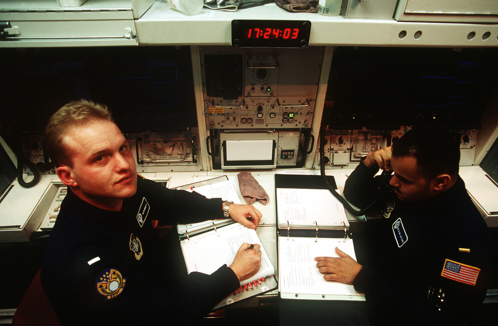 1ST LT. Glen Roberts and 2nd LT. Kelvin Jacobs from the 90th Missile Wing/Minuteman Crew read their manuals and perform daily missile tests inside the Missile Procedures Trainer