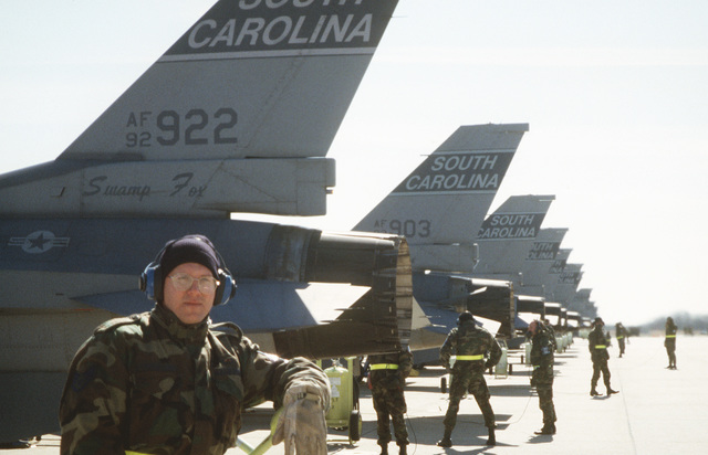A line of F-16 Fighting Falcons with fire bottles and personnel standing fire guard at the launch sequence during the 169th Fighter Wing Operational Readiness Inspection