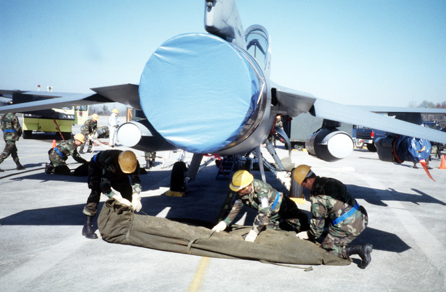 A three member crash recovery team unpacks one of the air bags used to lift the F-16 during the 169th Fighter Wing Operational Readiness Inspection