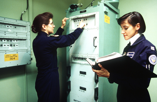 CAPT. Bonita Nolan and CAPT. Wendy McNiel from the 90th Missile Wing/Minuteman Crew, reset a tripped circuit breaker in the Missile Procedures Trainer. The Inspector General Team tested the ability of the base to respond to battle conditions, power outages, mobility deployments, aircraft and automobile accidents, hostage situations, bomb threats, armed robberies, terrorism, and communication problems