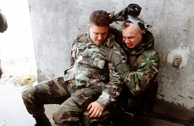 """While STAFF SGT. Patrick Bell from the 90th Security Police Squadron supports the """"victim"""", SENIOR AIRMAN John Whitman from the 90th Missile Maintenance Squadron (MXS), he removes his gas mask to scream for help"""