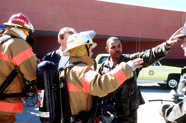 MASTER SGT. Allen Taylor, a member of the 90th Supply Squadron (SUPS), explains where the chemical was spilled and how the accident happened to Mr. Gregorio, a Rescue Firefighter from the 90th Civil Engineering Squadron. The Inspector General Team tested the ability of the base to respond to battle conditions, power outages, mobility deployments, aircraft and automobile accidents, hostage situations, bomb threats, armed robberies, terrorism, and communication problems