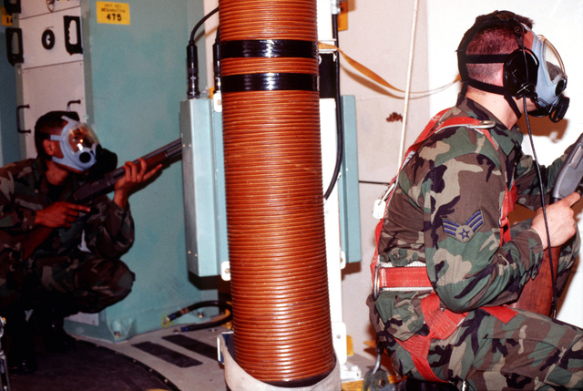 US Air Force Security Policemen SENIOR AIRMAN (SRA) Robert Hartwell (left) and Sergeant (SGT) Kirk Aytch from F E. Warren AFB, WY respond to a simulated hostage situation during the Operational Readiness Inspection (ORI) for the 90th Space Wing. SRA Hartwell and SGT Aytch are both armed with M870 12 gauge shot guns, and wearing MCU-2P gas mask as they take up positions inside the Launch Facility. (Duplicate image, see also DFST9801079 or search 960315F1247W002)